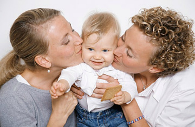 female couple kissing a child