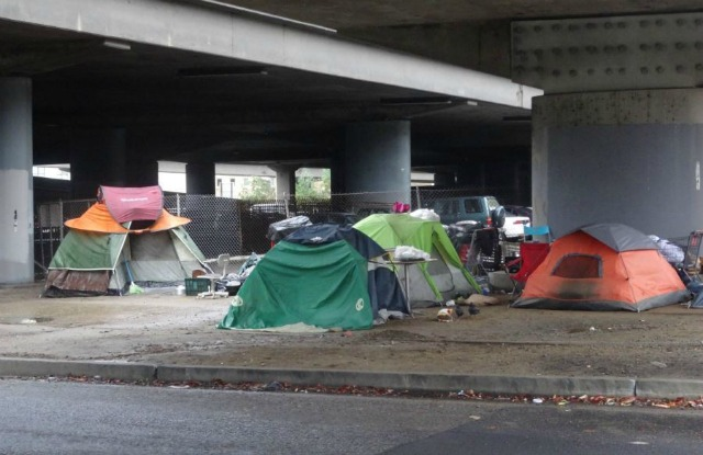 How can I help the homeless I see along highway intersections?